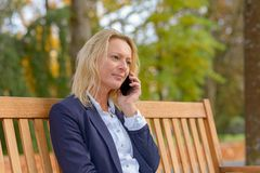 Attractive middle aged blond woman on a bench stock photography