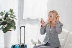 Businesswoman doing makeup before trip. Attractive middle aged businesswoman doing makeup before trip Stock Photo