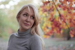 Attractive middle aged caucasian woman with green eyes at autumn park, smiling, alone. Casual wear. Precious age concept. royalty free stock images