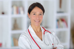 Attractive middle-aged female doctor smiling at camera Royalty Free Stock Photos