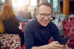 Attractive middle-aged man wearing glasses. Sitting in a restaurant holding his mobile phone as he smiles at the camera Royalty Free Stock Photos