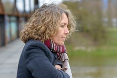Attractive middle-aged woman deep in thought. Leaning on the railing of a bridge looking down with a serious frown of contemplation stock photos