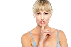 Attractive middle aged woman gesturing silence. Isolated against white background Royalty Free Stock Photo
