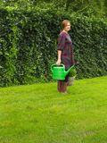 Attractive middle aged woman with a green watering can and basket plants in her hands. stock photos