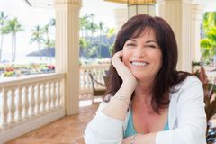 Attractive Middle Aged Woman Relaxing On a Tropical Patio stock photos