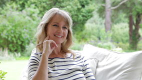 Attractive Middle Aged Woman Sitting Outdoors And Smiling