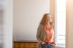 Middle-aged woman staring out of a window. Attractive middle-aged woman standing with her hands in her pockets of her jeans staring out of a window with a Stock Photos