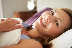 Attractive Middle Aged Woman Waking Up In Bed Royalty Free Stock Image