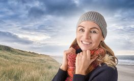 Attractive middle-aged woman wearing a knitted cap. And colorful red woollen scarf held up around her neck standing smiling happily at the camera outdoors on a stock photos