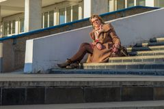 Attractive middle-aged woman wearing stylish coat and shoes sitting with bag on stairs step of office building in early spring at. Sunset. Street city portrait royalty free stock photography