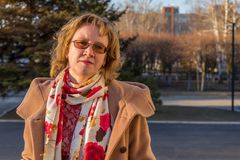 Attractive middle-aged woman wearing stylish coat walking around town in early spring at sunset. Street city portrait, fashion royalty free stock photo