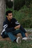Young Arab Teen Model Posing in Nature at the Park. Attractive Middle Eastern Male Model Posing and Smiling for the Camera Outside Stock Photo