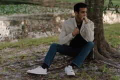 Young Arab Teen Model Posing in Nature at the Park. Attractive Middle Eastern Male Model Posing and Smiling for the Camera Outside Royalty Free Stock Photo