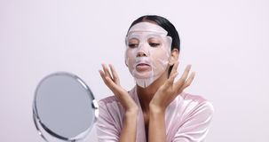 Pretty young woman in sheet face mask