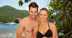 Attractive millennial couple standing at the beach smiling while on cruise Stock Photography