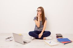 Attractive minded female student in striped t-shirt and jeans si. Tting on the floor studying and thinking about entering the university royalty free stock photo