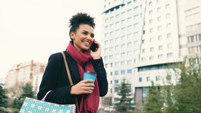 Attractive mixed race business woman talking smartphone and drinking coffee walks in city street with shopping bags stock photo