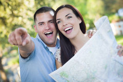 Attractive Mixed Race Couple Looking Over Map Outside Together Royalty Free Stock Photo