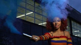 Attractive mixed-race girl clubbing in cloud of blue smoke, self-expression stock video