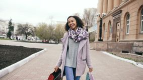 Attractive mixed race girl dancing and have fun while walking down the street with bags. Happy young woman walking after stock photos