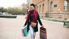 Attractive mixed race girl dancing and have fun while walking down the street with bags. Happy young woman walking after stock image