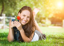 Attractive Mixed Race Girl Holding Flower Portrait Laying in Gra Stock Photo