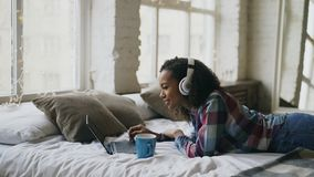 Attractive mixed race girl listen to music while surfing social media on laptop lying on bed. At home Stock Image