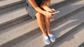 Attractive Mixed Race Student Girl Typing Text on Mobile Phone Sitting on Old Library Stairs. 4K. Attractive Mixed Race Student Girl Typing Text on Mobile Phone stock footage