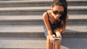 Attractive Mixed Race Student Girl Typing Text on Mobile Phone Sitting on Old Library Stairs. 4K. Attractive Mixed Race Student Girl Typing Text on Mobile Phone stock video footage
