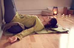 Attractive mixed race woman doing restorative yoga. Serene lady relaxing and meditating on a yoga mat in a cosy house Stock Photography