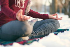 Attractive mixed race woman doing yoga in nature at winter time. Serene lady relaxing and meditating doing yoga poses Stock Photo