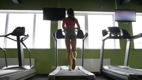 Attractive mixed race woman running on the treadmill in the sport gym. Attractive mixed race woman running on the treadmill in the sport gym in slow motion stock footage