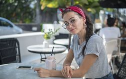 Attractive model in bandana and round glasses posing at the table of street cafe. Attractive model in red bandana and round glasses posing at the table of street royalty free stock photography