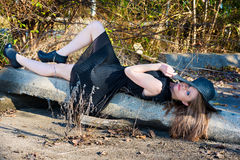 Attractive model in black pleated dress relaxes outide Stock Photo