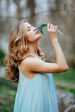 Attractive model in blue dress smell snowdrop flowers in the spring forest Stock Photo