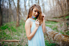 Attractive model in blue dress smell snowdrop flowers in the spring forest Stock Images