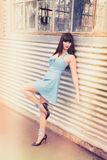 Woman in blue latex dress. A beautiful woman in blue latex dress and high heels leaning on wall Royalty Free Stock Photos