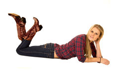 Attractive model laying down wearing cowboy boots smiling Royalty Free Stock Photography