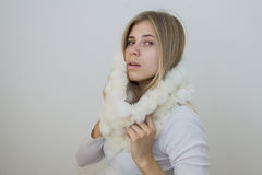 Attractive model  in lwhite fur boa. Woman portrait wrapping herself in lapin mauve scarf Royalty Free Stock Image