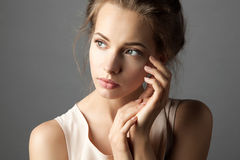 Attractive model with nude make up. Portrait of a young elegant woman with natural make-up touching her face on gray background Stock Photography