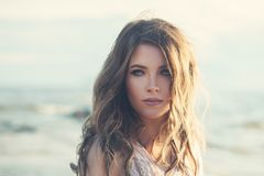 Attractive Model with Perfect Makeup and Wavy Colored Hair. Outdoors. Young Woman Walking on the Coastline royalty free stock image