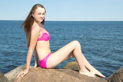 Attractive model in pink bikini sitting on stone at rocky beach Royalty Free Stock Photo