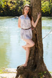 Attractive model relaxes by a tree beside small river Stock Photos