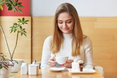 Attractive model sits in chair and looks in cup of coffee. Dreaming girl with blond hair wears white dress, holds cup in two hands stock image