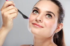 Attractive model smiling while tidy up her make up Royalty Free Stock Photography