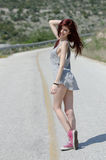 Attractive model standing in the middle of a mountain road royalty free stock image