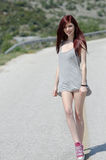 Attractive model standing in the middle of a mountain road royalty free stock photography