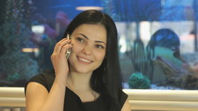 Attractive model talking on a smartphone indoors. Attractive model aged 20s sitting at a cafe and talking on a smartphone in the background blue aquarium stock video