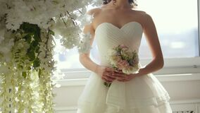 Attractive model in wedding dress with bride`s bouquet. Close up stock footage