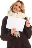 Attractive model in winter fashion holding a blank white sign Stock Images